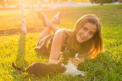 宠物和所有者概念-使用与在草的一只猫的女孩 免版税图库摄影