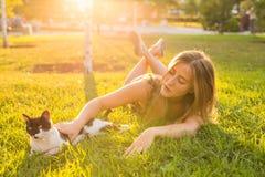 宠物和所有者概念-使用与在草的一只猫的美丽的女孩 库存图片