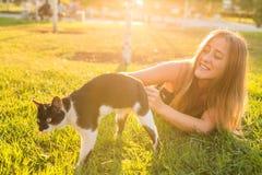 宠物和所有者概念-使用与在草的一只猫的美丽的女孩 库存照片