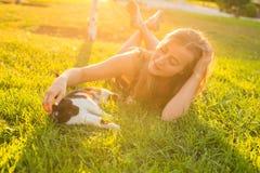 宠物和所有者概念-使用与在草的一只猫的美丽的女孩 免版税库存照片