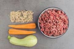 宠物食品的自然未加工的成份在灰色背景 库存照片