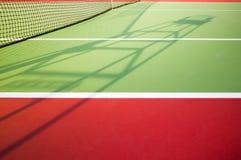 审判员椅子的阴影在绿色和红色硬地网球的与一部分的网 库存图片