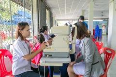 审查一个可爱的年轻人的女性Optictian护理在com的` s眼睛 图库摄影
