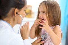 审查一个小女孩的医生由听诊器 免版税库存照片