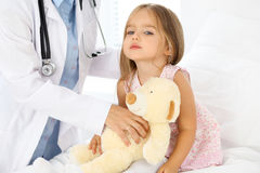审查一个小女孩的医生由听诊器 免版税库存图片