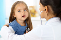 审查一个小女孩的医生由听诊器 图库摄影