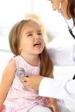 审查一个小女孩的医生由听诊器 库存图片