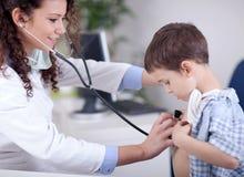 审查一个小男孩的年轻人微笑的友好的女性医生 图库摄影