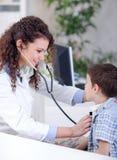 审查一个小男孩的年轻人微笑的友好的女性医生 免版税图库摄影