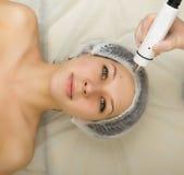 审查一个年轻女性客户的面孔美容师在温泉沙龙 得到rf举在美容院 专业人员 库存照片