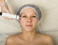 审查一个年轻女性客户的面孔美容师在温泉沙龙 得到rf举在美容院 专业人员 免版税库存图片