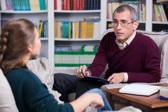 审查一名女性患者的精神病医生 免版税库存照片