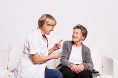 审查一名年长妇女的一位资深护士的演播室画象 库存图片