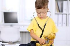 审查一名ntoy熊患者的小医生由听诊器 免版税库存图片
