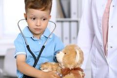 审查一名ntoy熊患者的小医生由听诊器 图库摄影