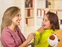 审查与一个听诊器和一个惊奇的小孩的美丽的微笑的医生在一家医院在办公室背景中 免版税库存照片