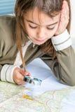 审查与寸镜的被集中的七岁的女孩地图 免版税库存图片