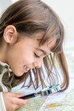 审查与寸镜的被集中的七岁的女孩地图 图库摄影