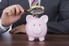 审查与放大镜的商人Piggybank 免版税库存照片