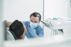 审查他的患者牙的被集中的男性牙医 库存照片