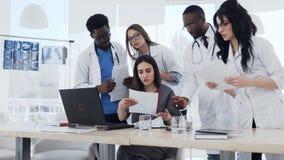 审查医疗报告的多种族专家的医生队在医院 有小组实习生和的医生 股票录像