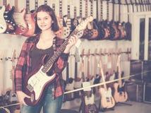审查各种各样的电吉他的好青少年的女孩 免版税库存照片
