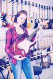 审查各种各样的电吉他的美丽的青少年的女孩 图库摄影