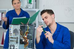 审查和修理计算机零件的队学生 免版税库存照片