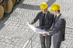 审查图纸的大角度观点的年轻男性建筑师由栏杆 免版税库存图片