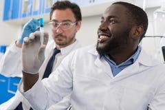 审查在注射器,混合种族的两位男性实验室科学家样品射入篡改In化学制品的实验室研究结果 免版税库存图片