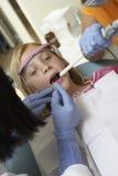 审查女孩的牙的牙医 免版税库存图片