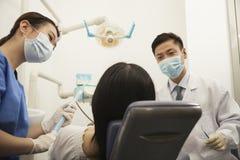 审查女性患者的牙医 免版税库存图片