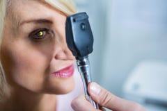 审查女性患者的验光师通过检眼计 库存图片