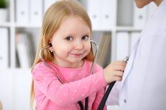审查她的医生的小女孩由听诊器 医疗保健,儿童患者信任概念 免版税图库摄影