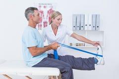 审查她的患者后面腿的医生 免版税库存图片