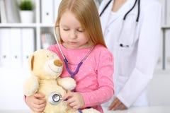 审查她的玩具熊的小女孩由听诊器 医疗保健,儿童患者信任概念 图库摄影