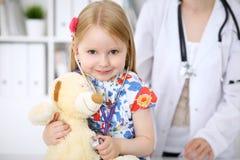 审查她的玩具熊的小女孩由听诊器 医疗保健,儿童患者信任概念 库存照片