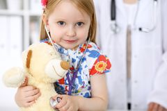 审查她的玩具熊的小女孩由听诊器 医疗保健,儿童患者信任概念 免版税库存图片