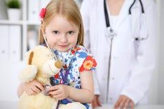 审查她的玩具熊的小女孩由听诊器 医疗保健,儿童患者信任概念 库存图片