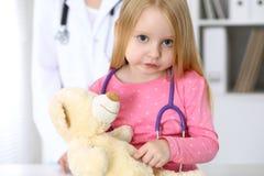 审查她的玩具熊的小女孩由听诊器 医疗保健,儿童患者信任概念 免版税库存照片