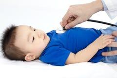审查小男孩的医生由听诊器 免版税库存照片