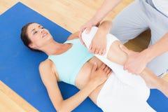 审查少妇腿的理疗师 免版税库存照片