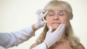 审查年长女性耐心皮肤的皮肤病学家,起皱纹撤除,秀丽 股票视频