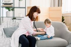 审查有仪器听诊器的,医疗保健,婴孩,婴孩规则健康检查的小儿科医生小女婴 图库摄影