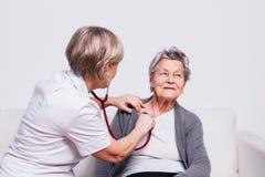审查有听诊器的一位资深护士的演播室画象一名年长妇女 免版税库存图片