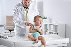 审查有听诊器的儿童的医生小男孩在医院 免版税库存照片