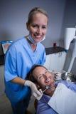 审查有工具的微笑的牙医一名年轻患者 库存照片