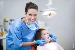 审查有工具的牙医一名年轻患者在牙齿诊所 库存图片