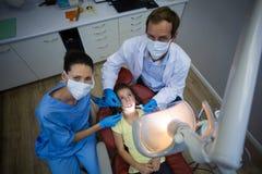 审查有工具的牙医一名年轻患者在牙齿诊所 免版税图库摄影