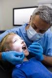 审查有工具的牙医一名年轻患者 库存图片